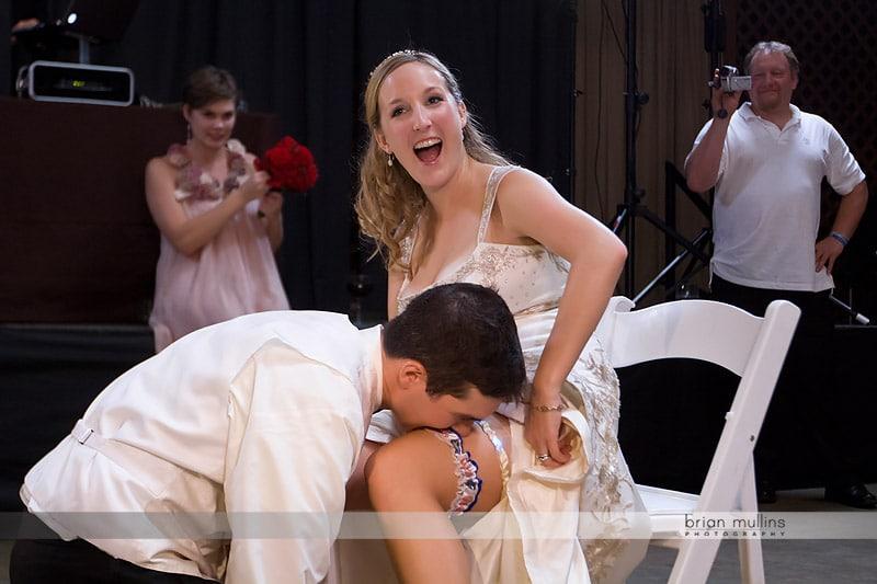 groom removing garter with teeth