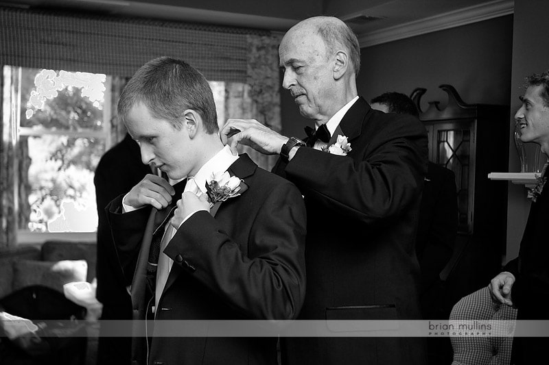 grooms father helping son get ready