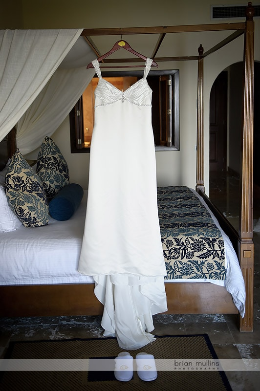wedding dress hanging on four poster bed