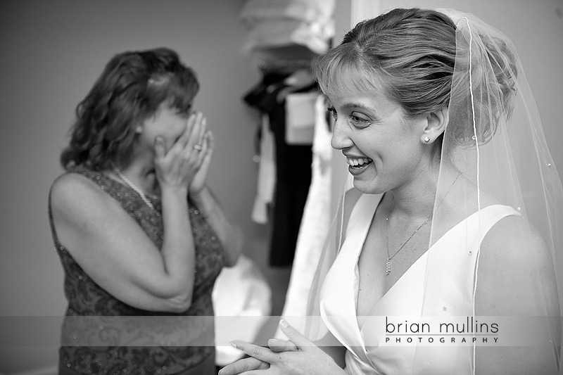 Mom crying after bride puts on dress