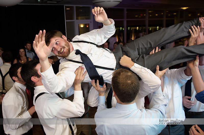 groomsmen lifting the groom