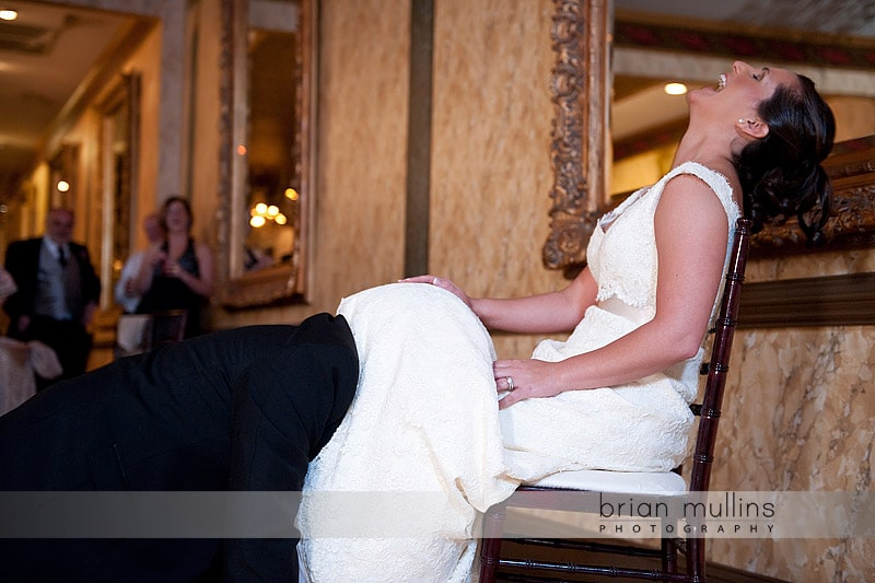 groom removing garter with mouth
