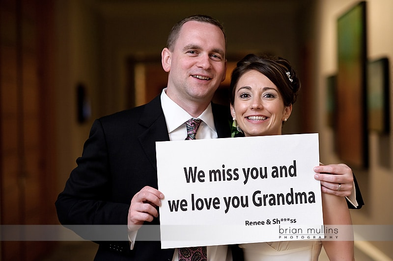 bride & groom holding a sign for grandma