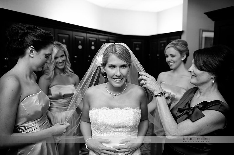 bride surrounded by bridesmaids while getting ready