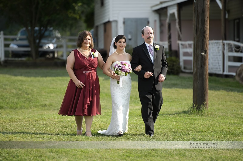 mom and dad walking bride down aisle
