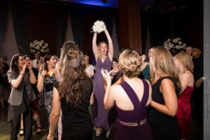 bridesmaid catching the bouquet during hte bouquet toss