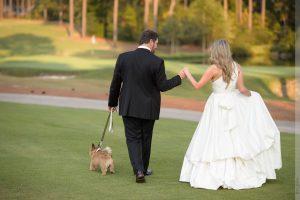 bride and groom walking dog