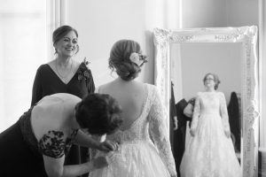brides mom helping her button dress