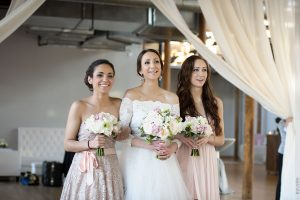bride walking down aisle with sisters