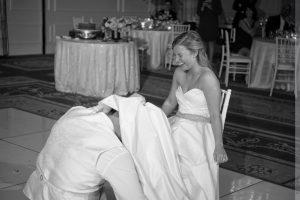 groom under dress getting garter
